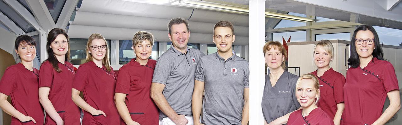 Gruppenbild: Das Team der Praxis für Implantologie und Oralchirurgie Dr. Jens Stoltz steht im Empfangsbereich der Praxis.